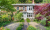 The property is approached across a pretty front garden with driftwood path