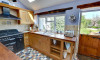 Attractive kitchen which has plenty of wooden work surfaces and door leading to the garden