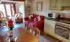 The open plan lounge/diner features slate floors, bright rugs, beamed ceilings and a stable door