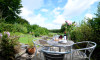A large terraced garden with lawns and patios offers a lovely outdoor space for relaxation and alfresco dining