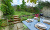 The patio with the fully enclosed pretty lawned garden beyond