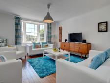 The spacious living room with its bay window and white leather sofas and chairs provides a cosy place to unwind