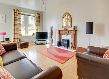 Modern living room has comfy leather seating flanking the attractive fireplace with electric wood burning style stove, perfect for cosy evenings