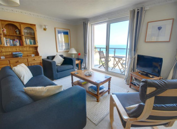 Cosy sitting room which is open plan with outstanding views through the large picture windows.