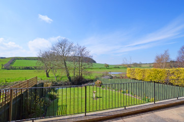 The view from the raised veranda across the fields and the stream