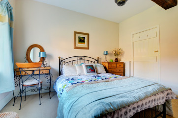 A pretty double bedroom with a wrought iron double bed