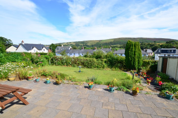 There is a good sized patio and lawned garden to the rear of the bungalow, with views over houses to the surrounding hills