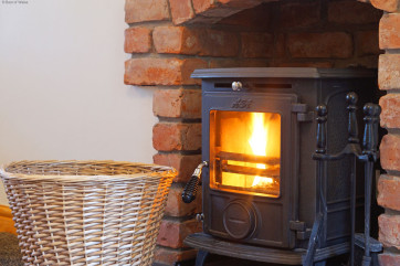 Large, warm and inviting lounge with comfortable seating & logburner