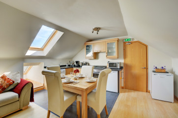 The kitchen also benefits from a table and chairs, ideal for dining