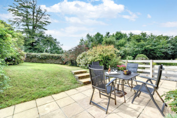 Enjoy dining on the terrace overlooking the extensive lawned garden at The Oaks, a beautiful Devon countryside cottage