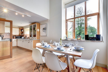 Bright and airy, the kitchen and dining room at The Oaks is the perfect place to gather for a delicious meal on a family holiday to Devon