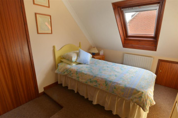 View of bedroom 4 with a single bed, sloped ceiling with velux window.