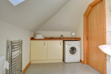 The bathroom also has a handy utility area with sink and washing machine