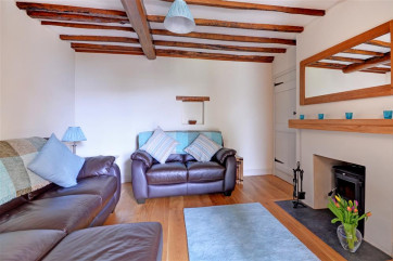 The sitting room with comfy seating and open beams