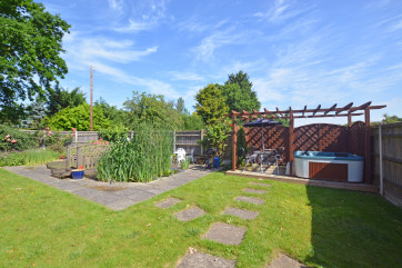 Nicely lawned area with a hot tub on a decked area