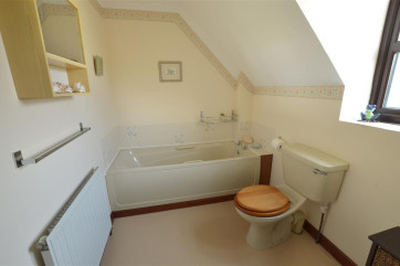 View of bathroom showing the bath, toilet and radiator.