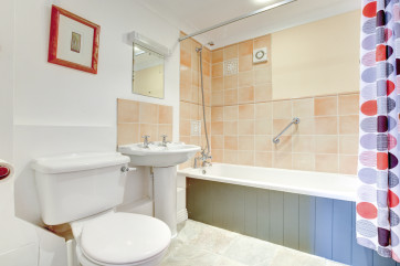 A contemporary bathroom with full sized bath and shower overhead
