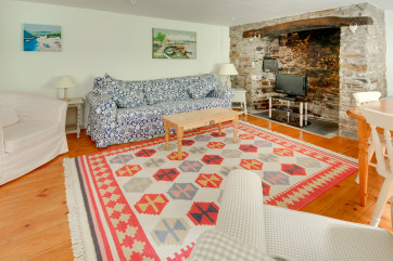 Charming living/dining room with an impressive stone inglenook and comfy sofa