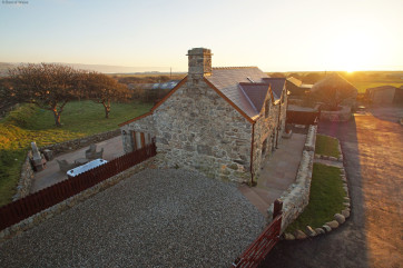 Hafod cottage with the sun setting over the sea