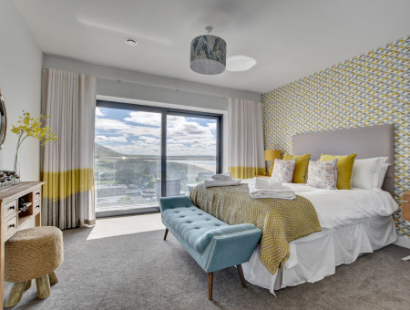 The spacious master king size bedroom has been stylishly decorated in yellows and greys and boasts sliding doors to the second floor balcony