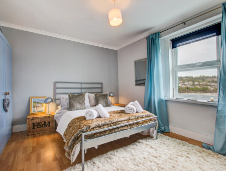 First floor: Bedroom 1: Large window with river views, double bed, bedside cabinet, bedside light, flatscreen TV with DVD player, bespoke built in wardrobe.