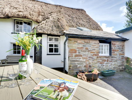This charming 18th century Grade II listed cottage with a thatched roof and roses in the garden is picture perfect