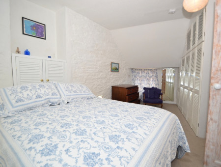 Master bedroom: Built in wardrobes, wall mounted full length mirror, chair, vintage chest of drawers, two bedside tables and lamps, selection of books, window seat with cushions. En-suite bathroom.