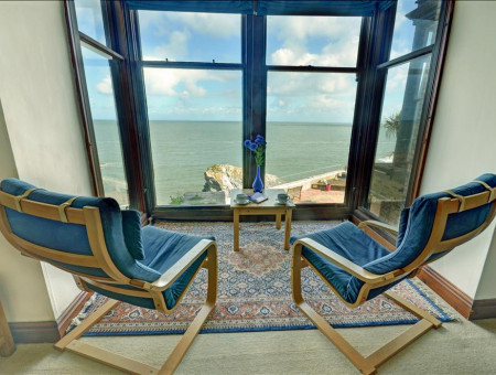Huge bay windows look out over a fabulous vista of the ocean
