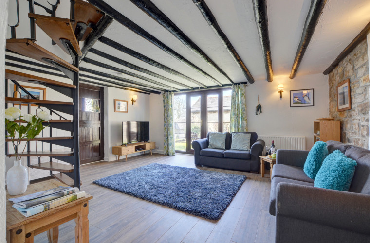 The spacious beamed open plan living area has a spiral staircase to the first floor and a French window to small side lawn with garden furniture