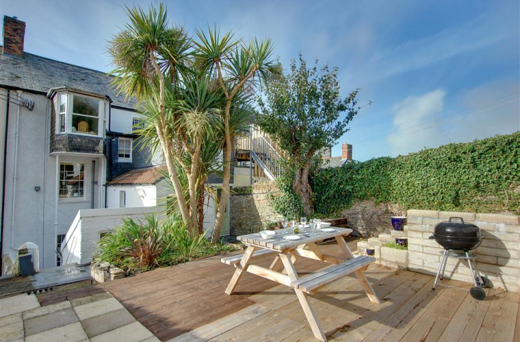 A fully enclosed rear patio and terraced garden is ideal for enjoying a relaxing outdoor dining experience