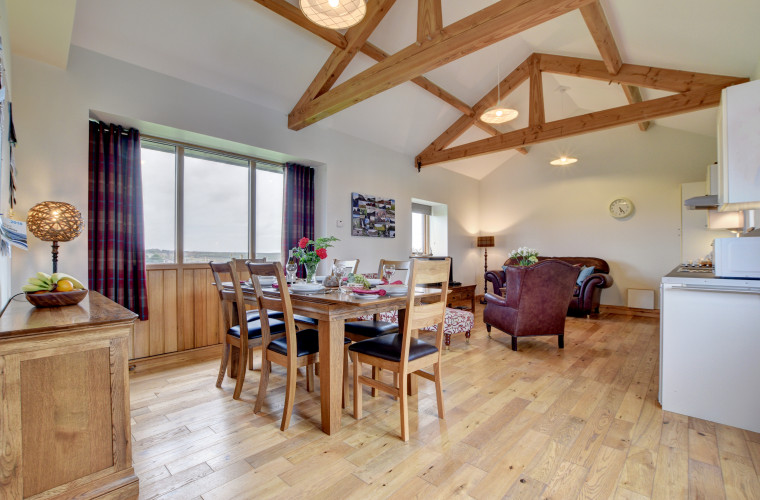 The spacious open plan living/dining/kitchen looks out over a picturesque valley
