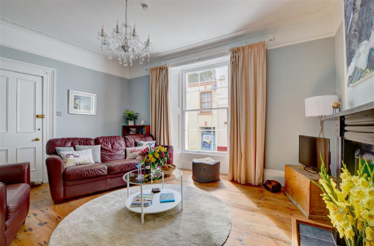 The spacious living room has a high cornice ceiling, original Georgian windows, a feature Victorian fireplace and original wooden floor