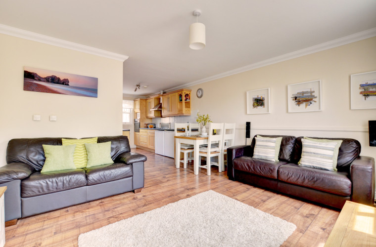 The light, spacious, and stylish open plan living room has comfy leather sofas