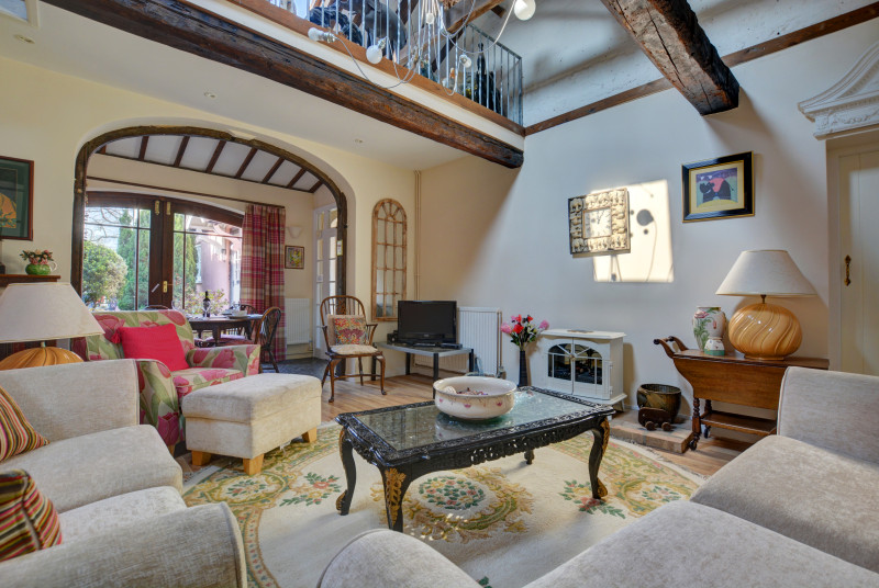 Charming sitting room with sofas, chairs and a dining area through the archway