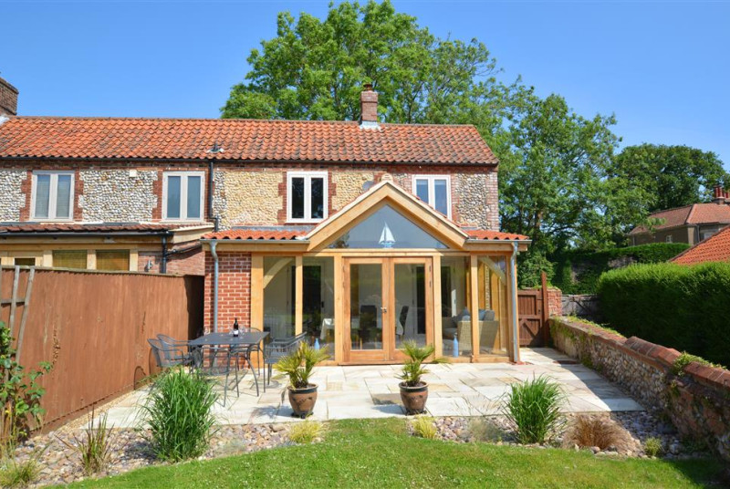 Exterior image of this lovely brick and flint cottage