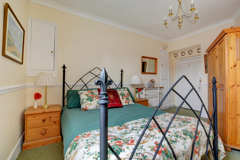 A charming double bedroom with a wrought iron double bed