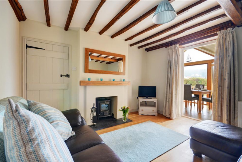 Sitting room with comfortable seating and a woodburner