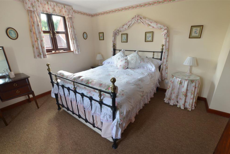 View of double bedded room dressed with pretty floral bed linen.