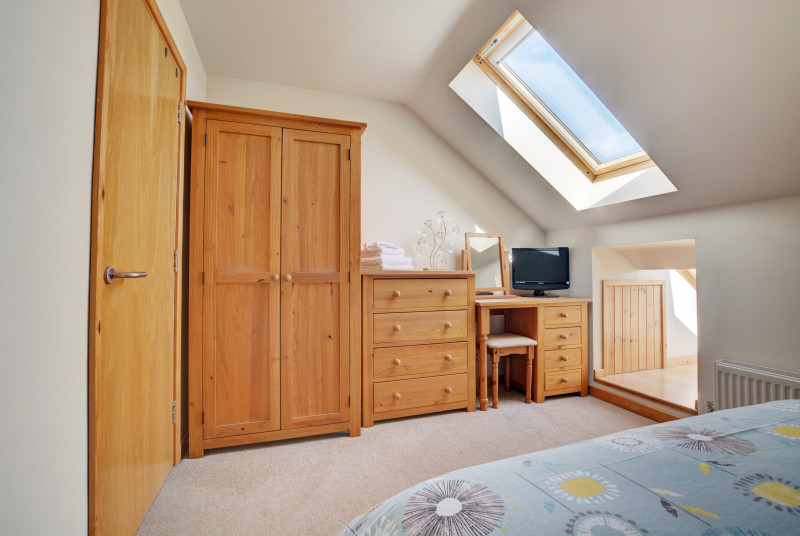 A wardrobe and dressing table provides ample storage in the bedroom