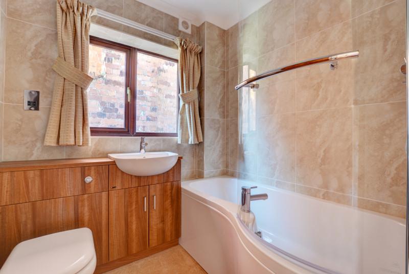 The ground floor bathroom has a bath and an over-bath shower
