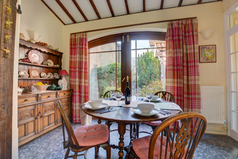 Tradionally furnished dining room with table, chairs and doors leading to the garden, perfect for family meals