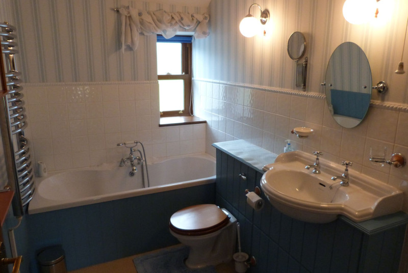Attractive bathroom with bath, WC and separate electric shower cubicle.