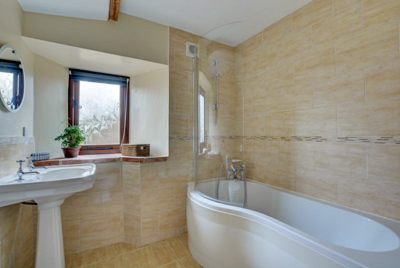 The main bathroom with curved bath and over bath shower.