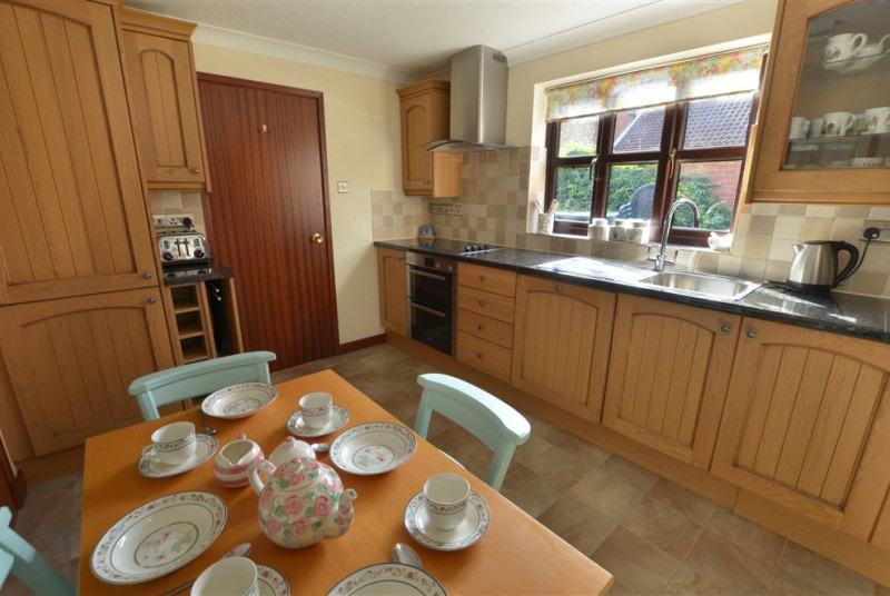 View of kitchen with the cupboards, breakfast table and door through.