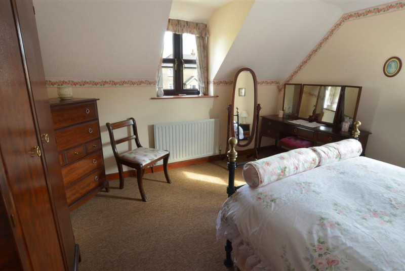 Bedroom 1 with a dressing table, full length freestanding mirror, chair, wardrobe and chest of drawers in dark wood.