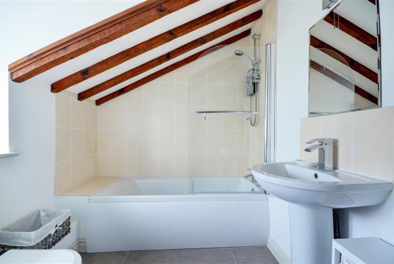 Bathroom with bath and over bath shower