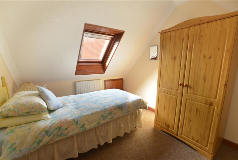 View of single bedroom with double wardrobe and velux window.
