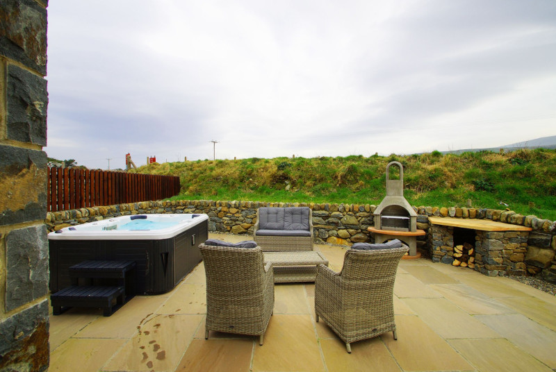 Private hot tub with rattan settee, 2 chairs, table and BBQ / log burner