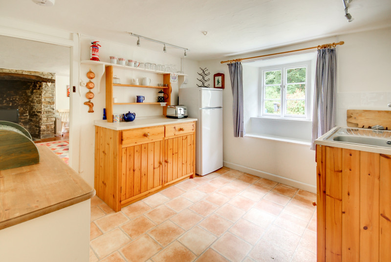 The country style kitchen is fitted in pine and to the rear of the cottage