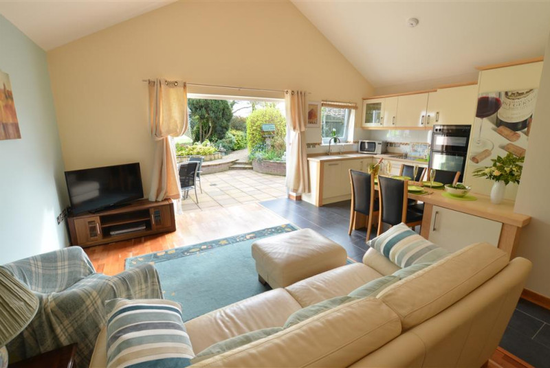 The room is a large and spacious open plan room with french doors out onto the patio